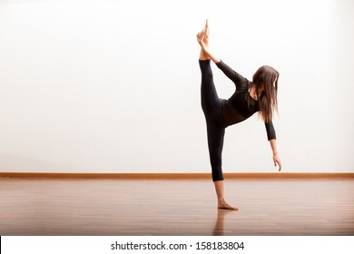 Pretty Hispanic female jazz dancer practicing some dance moves in a dance academy