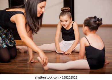Pretty Hispanic little girls listening to her dance instructor directions during a dance class