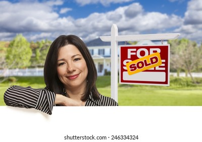 Pretty Hispanic Woman Leaning on White in Front of Beautiful House and Sold For Sale Real Estate Sign.