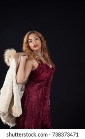 Pretty Hispanic woman in  a red dress, looking thoughtful as she holds a fur coat over her shoulder