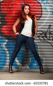 Pretty hispanic young woman posing outdoors in an urban setting with a graffiti wall background.