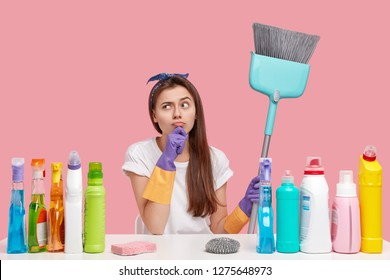 Pretty housemaid has intention, looks thoughtfully aside, dressed in caual clothes, holds broom, does housework, bought much chemical supplies, isolated over pink background. Cleaning and hygiene