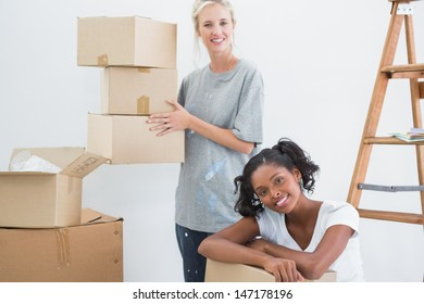 Pretty housemates carrying cardboard moving boxes and looking at camera in new home