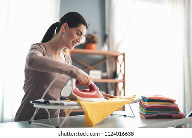 Pretty housewife in good mood with iron and colorful clothes. She is concentrated on doing homework with joy