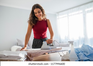 Pretty housewife in good mood with iron and colorful clothes. She is concentrated on doing homework with joy. Young woman ironing clothes on ironing board
