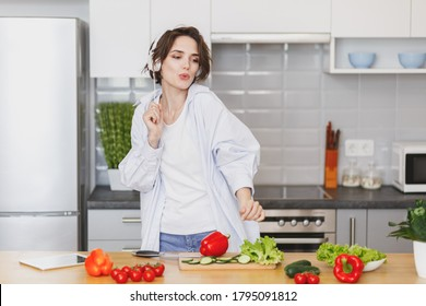 Pretty housewife woman in casual clothes preparing vegetable salad cooking food in light kitchen at home. Dieting healthy lifestyle concept. Listen music with headphones, dancing fooling around