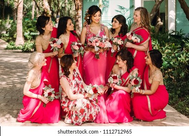 Pretty Indian bridesmaids in red sari stand around beautiful bride in pink sari posing outside