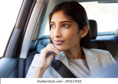 pretty indian business executive daydreaming in a car
