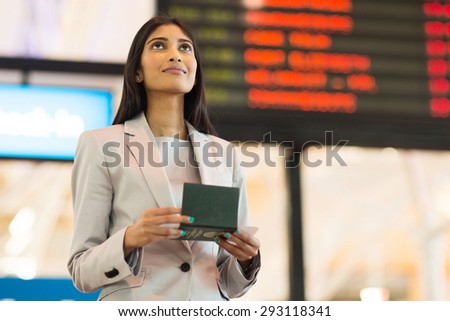 pretty indian business woman checking flight information at airport