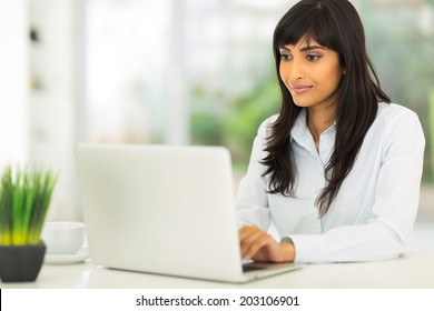 pretty indian businesswoman using computer in office