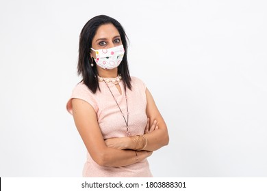 Pretty Indian female wearing Covid-19 protection mask. Woman with serious expression and arms folded with a professional look.