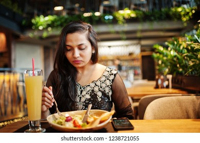 Pretty indian girl in black saree dress posed at restaurant, sitting at table with juice and salad.