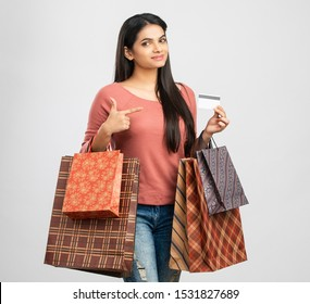 Pretty Indian girl with shopping bags with credit card.