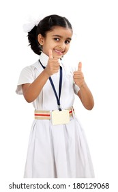 Pretty Indian little school girl showing thumbs up against white background