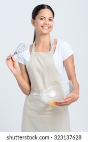 Pretty indian woman chef holding a whisk and glass bowl with eggs