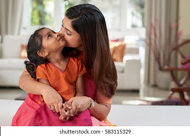 Pretty Indian woman kissing her little girl on cheek tenderly while spending free time together in living room