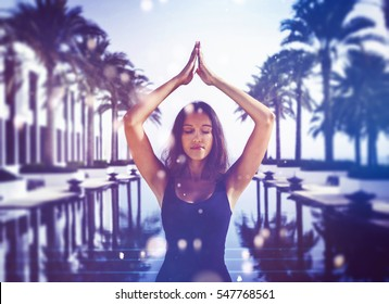 Pretty Indian woman practicing yoga on summer vacation standing meditating with closed eyes at the end of a long tranquil resort pool lined with tropical palms in a healthy lifestyle or travel concept