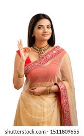 Pretty Indian young girl showing best hand sign in saree on white..