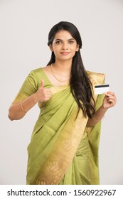 Pretty Indian young woman with credit card in traditional saree.