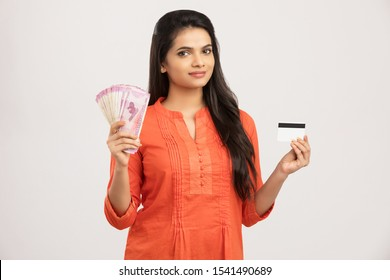 Pretty Indian young woman with Indian currency with credit card.