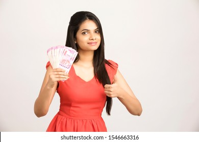 Pretty Indian young woman with Indian currency.