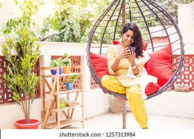 Pretty Indian young woman relaxing in a hanging chair with mobile phone