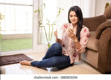 Pretty Indian young woman using phone with coffee cup at living room.