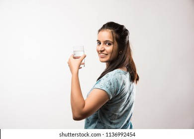 pretty Indian/Asian girl holding glass of plain water, standing isolated over white background