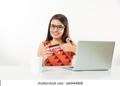 Pretty Indian/Asian Girl online shopping using Debit/Credit card on laptop computer at table, over white background
