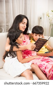 Pretty Indian/Asian Mother reading book for kids while sitting over sofa at home