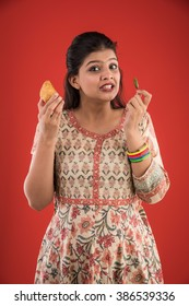 Pretty Indian/asian young girl eating Samosa Snack while standing isolated over red background