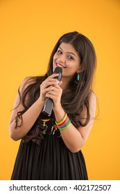 Pretty Indian/asian young girl singing in a wireless Mic while standing isolated over yellow background