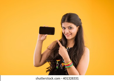 Pretty Indian/asian young girl using Smartphone, isolated over yellow background