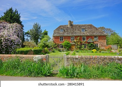 A pretty individual red brick with slate roof Cotswold country cottage in the heart of the Cotswolds, Gloucestershire, United Kingdom