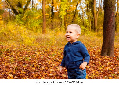 Pretty infant in autumn park among trees