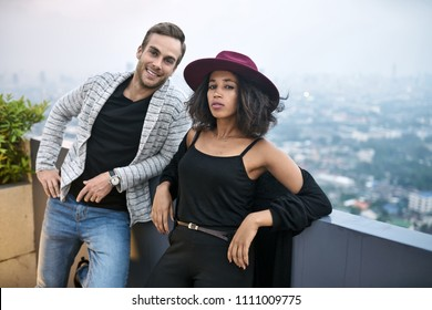 Pretty interracial couple on the balcony on the background of the cityscape. Black girl in a crimson hat and her smiling white boyfriend looking into the camera. They wears black and gray cardigans.