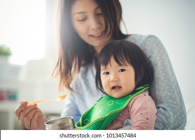 Pretty japanese woman feeding her baby daughter with spoon