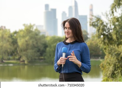 Pretty journalist is reporting on a business center background