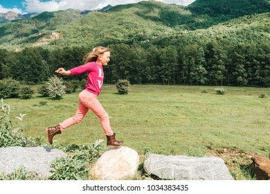 Pretty kid girl resting in mountains, jumping, running, having fun, wearing pink clothes. Arms wide open