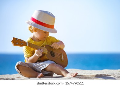 Pretty kid plays on ukulele or small guitar at white sandy beach with blue water