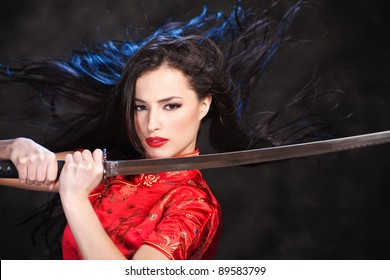 Pretty kimono woman in action with katana/sword