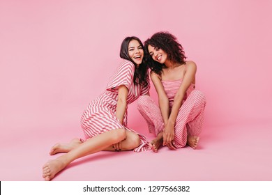 Pretty ladies in wide striped pants laughing happily and having fun on floor in pink studio
