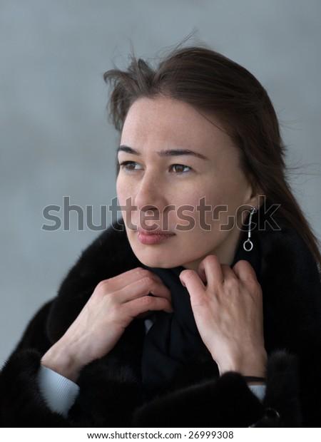 Pretty lady adjusting her fur coat' collar - portrait on gray background