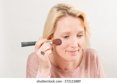 Pretty lady applying blush with a brush over a white background
