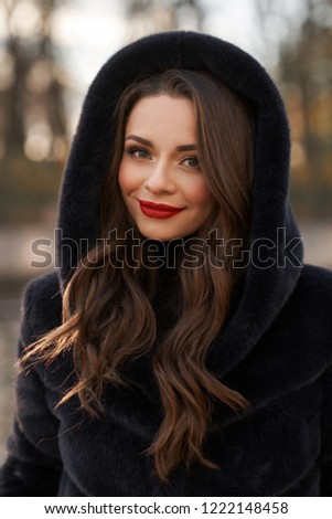 Pretty lady in black fur coat with hood standing and posing at city street. Fashionable woman. Closeup face portrait.