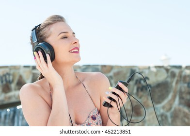 Pretty lady enjoying listening to music on headphones with eyes closed outside with copy text space