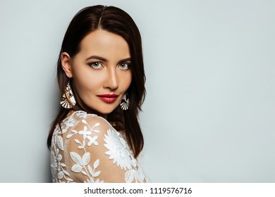 Pretty lady. Fashion model portrait. Young beautiful brunette woman dressed on stylish white dress with professional make up. Earrings in the ears.