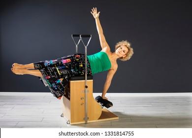 Pretty Lady Holding Balance on Aura Pilates Combo Chair