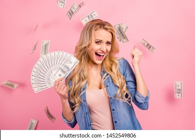 Pretty lady holding bucks bills flying everywhere wear denim outfit isolated pink background