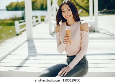 Pretty lady sitting on a summer beach. Cute girl eats the ice cream. Brunette in a pink sweater and gray jeans/